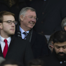 Manchester United's former manager Alex Ferguson, centre left, smiles as he takes his seat before the team's English Premier League soccer match between Manchester United and Liverpool at Old Trafford Stadium, Manchester, England, Sunday Dec. 14, 2014