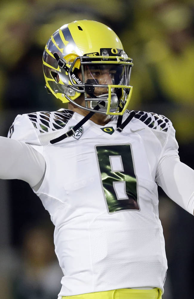 Oregon quarterback Marcus Mariota warms up before an NCAA college football game against Stanford, Thursday, Nov. 7, 2013, in Stanford, Calif