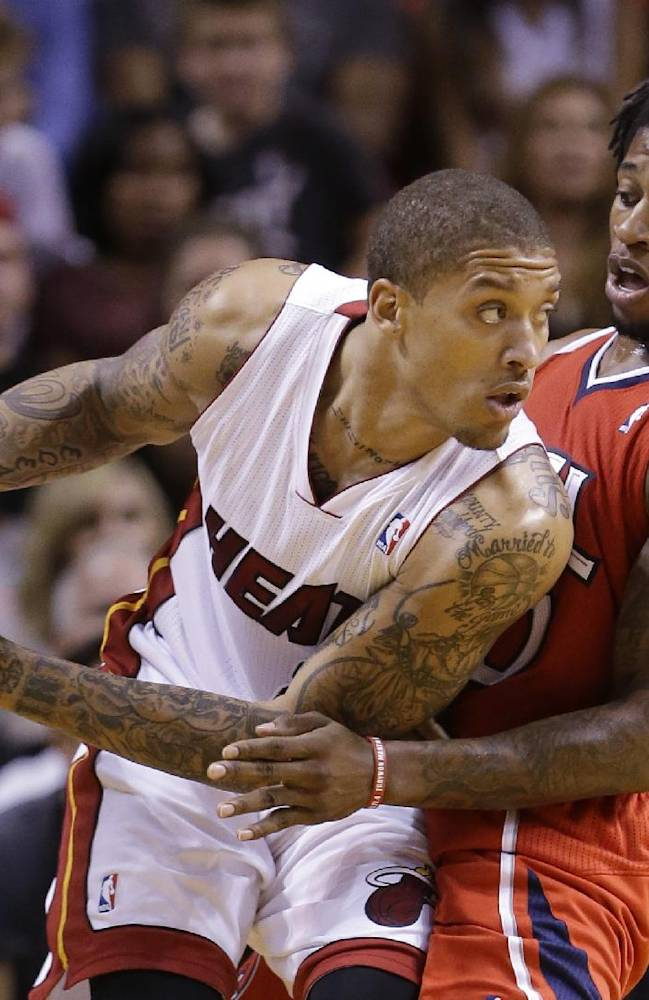 Miami Heat forward Michael Beasley, left, looks for an open teammate past Atlanta Hawks forward Cartier Martin during the second half of an NBA basketball game, Tuesday, Nov. 19, 2013 in Miami. The Heat defeated the Hawks 104-88