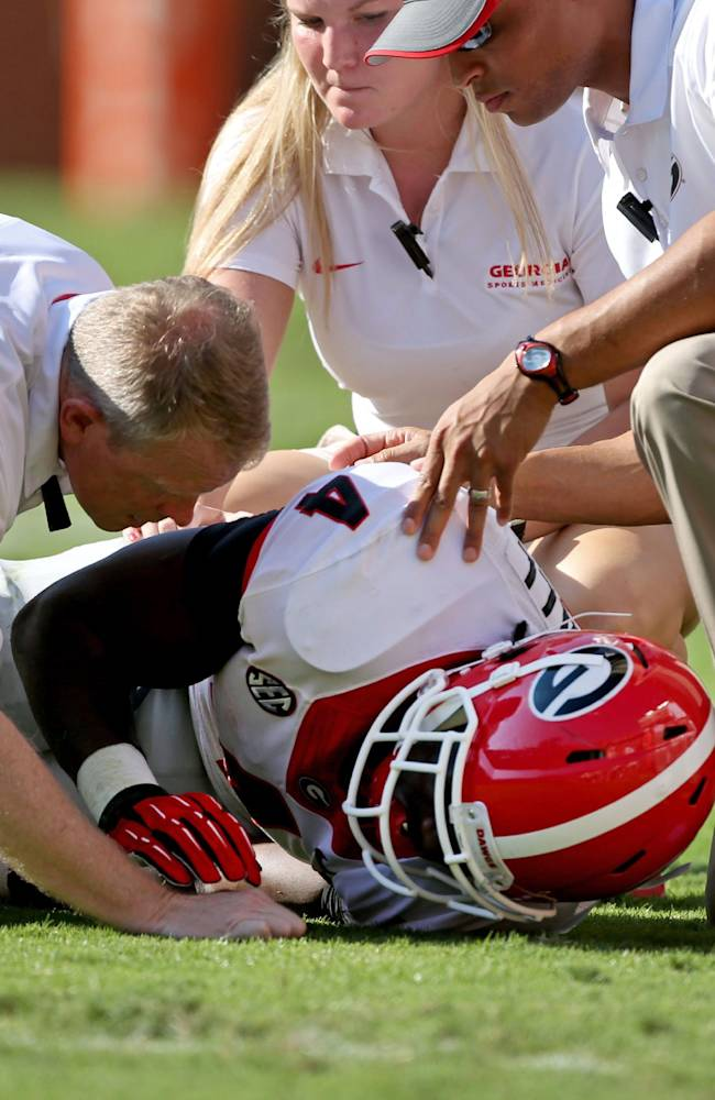 Georgia trainers talk with Georgia's Keith Marshall (4) after he was injured in the first half of an NCAA college football game in Knoxville, Tenn., Oct. 5, 2013