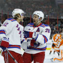 New York Rangers' Carl Hagelin, left, of Sweden, celebrates with Dominic Moore, center, after Hagelin's goal against Philadelphia Flyers' Ray Emery during the first period of a preseason NHL hockey game, Tuesday, Sept. 30, 2014, in Philadelphia. (AP Photo/Matt Slocum)