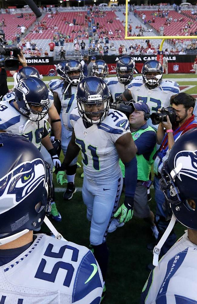 The Seattle Seahawks huddle prior to a NFL football game against the Arizona Cardinals, Thursday, Oct. 17, 2013, in Glendale, Ariz