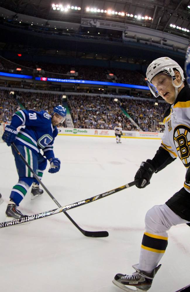 Vancouver Canucks' Ryan Stanton, right, battles Boston Bruins' Carl Soderberg, second right, of Sweden, for the puck as Bruins' Patrice Bergeron, left, and Canucks' Chris Higgins watch during first period NHL hockey action in Vancouver, British Columbia, on Saturday, Dec. 14, 2013