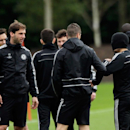 Chelsea's Eden Hazard, right, stands with his hat pulled down over his face, next to Fernando Torres, center, and Branislav Ivanovic, left, as they gather together at the start of a training session at their facilities, in Stoke d'Abernon, near London, Mo