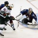 Minnesota Wild right wing Nino Niederreiter, front left, of the Czech Republic, is checked by Colorado Avalanche defenseman Tyson Barrie, back left, as Avalanche goalie Semyon Varlamov, of Russia, deflects Niederreiter's shot in the third period of the Wi