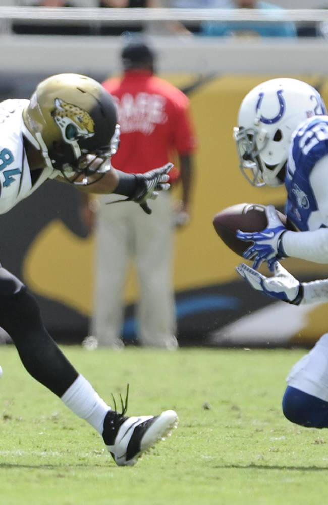 Indianapolis Colts cornerback Darius Butler (20) intercepts a pass as it bounces out of the hands of Jacksonville Jaguars wide receiver Cecil Shorts (84) during the first half of an NFL football game in Jacksonville, Fla., Sunday, Sept. 29, 2013. Butler returned the interception for a 41-yard touchdown