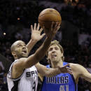 San Antonio Spurs' Tony Parker (9), of France, shoots around Dallas Mavericks' Dirk Nowitzki (41), of Germany, during the first quarter of Game 1 of the opening-round NBA basketball playoff series on Sunday, April 20, 2014, in San Antonio. (AP Photo/Eric Gay)