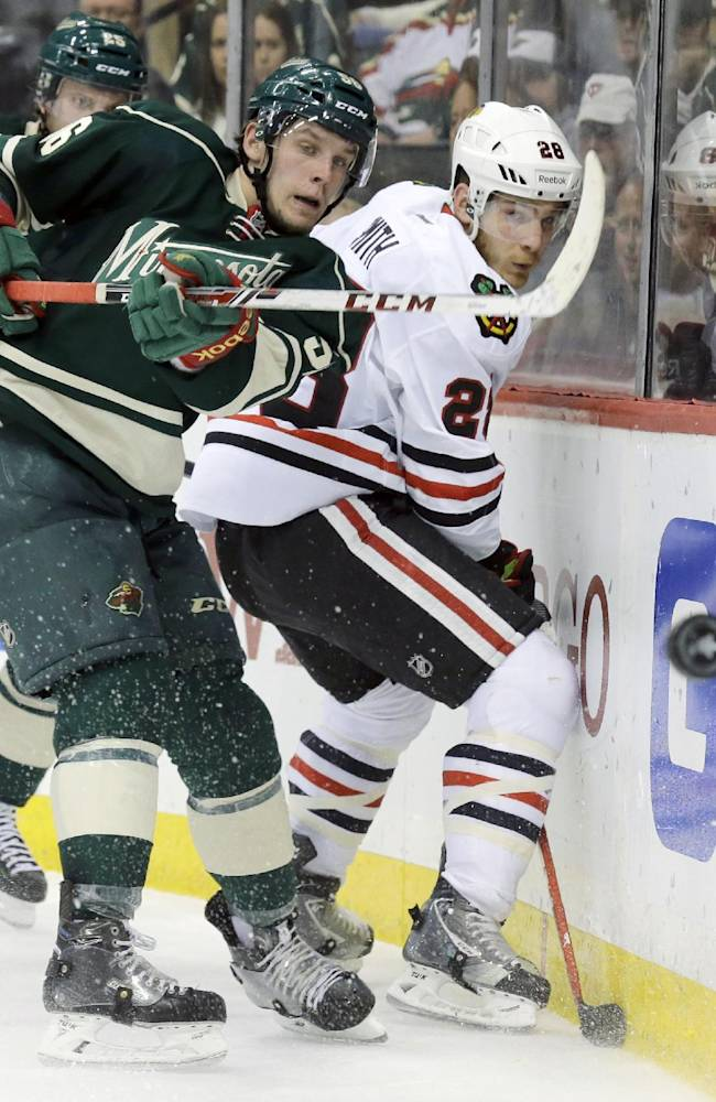 Minnesota Wild left wing Erik Haula, left, of Finland, and Chicago Blackhawks right wing Ben Smith (28) chase the puck during the second period of Game 6 of an NHL hockey second-round playoff series in St. Paul, Minn., Tuesday, May 13, 2014. The Blackhawks won 2-1 in overtime
