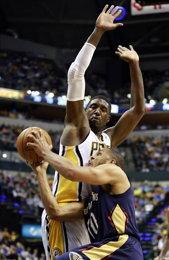 New Orleans Pelicans guard Eric Gordon, front, collides with Indiana Pacers center Roy Hibbert while driving to the basket during the second half of an NBA basketball game in Indianapolis, Saturday, Jan. 4, 2014