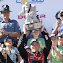 Chris Buescher hoists the trophy as he celebrates his win in Victory Lane after winning the NASCAR Xfinity series auto race, Saturday, May 30, 2015, at Dover International Speedway in Dover, Del. (AP Photo/Nick Wass)