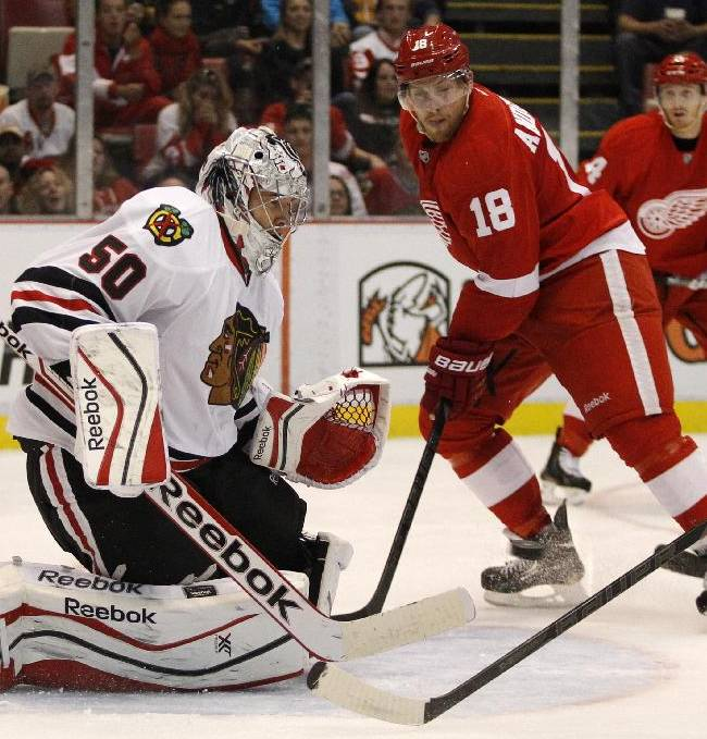 Chicago Blackhawks' Corey Crawford (50) gets in front of the puck as Detroit Red Wings' Joakim Andersson (18) waits for a rebound in the second period of a preseason NHL hockey game Sunday, Sept. 22, 2013 in Detroit