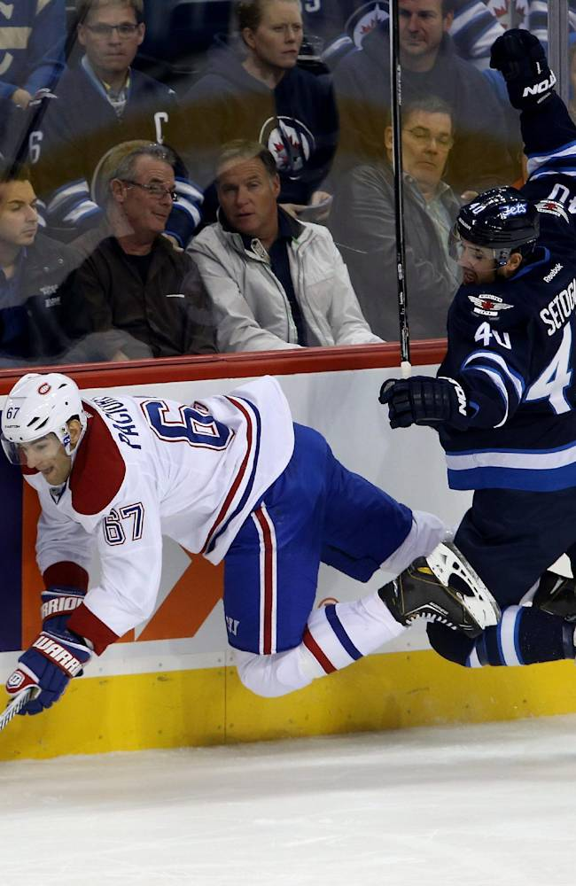 Montreal Canadiens' Max Pacioretty (67) is tripped up along the boards by Winnipeg Jets' Devin Setoguchi (40) during the first period of an NHL hockey game in Winnipeg, Manitoba, Tuesday, Oct. 15, 2013