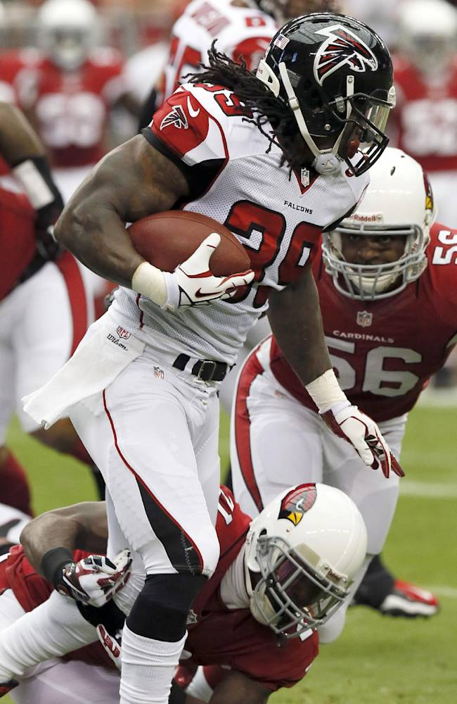 Atlanta Falcons running back Steven Jackson (39) escapes the reach of Arizona Cardinals cornerback Patrick Peterson, bottom, during the first half of an NFL football game Sunday, Oct. 27, 2013, in Glendale, Ariz