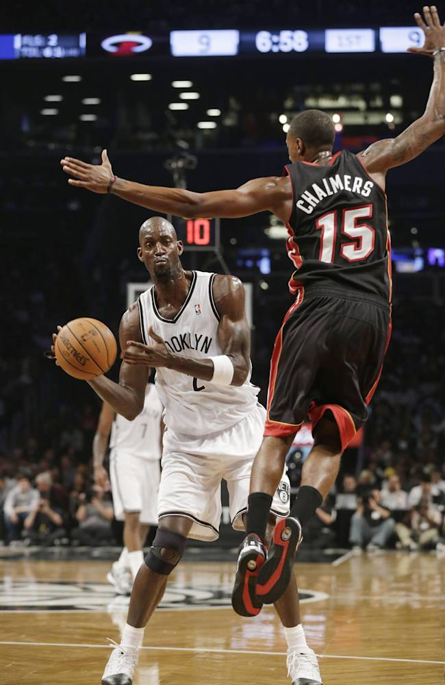 Brooklyn Nets' Kevin Garnett (2) passes away from Miami Heat's Mario Chalmers (15) during the first half of an NBA basketball game Thursday, Oct. 17, 2013 in New York
