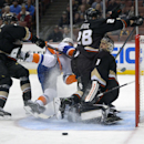 New York Islanders right wing Michael Grabner, second from left, of Austria, runs into Anaheim Ducks goalie Jonas Hiller, of Swizterland, along with defenseman Hampus Lindholm, left, of Sweden, and defenseman Mark Fistric as he tries to score during the f