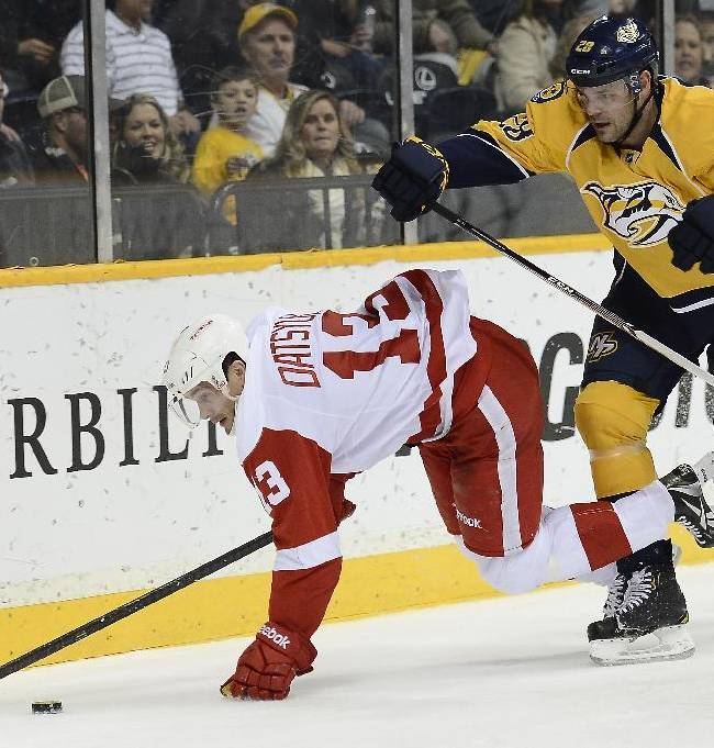 Detroit Red Wings center Pavel Datsyuk (13), of Russia, trips over Nashville Predators forward Paul Gaustad (28) while chasing down the puck in the first period of an NHL hockey game on Monday, Dec. 30, 2013, in Nashville, Tenn