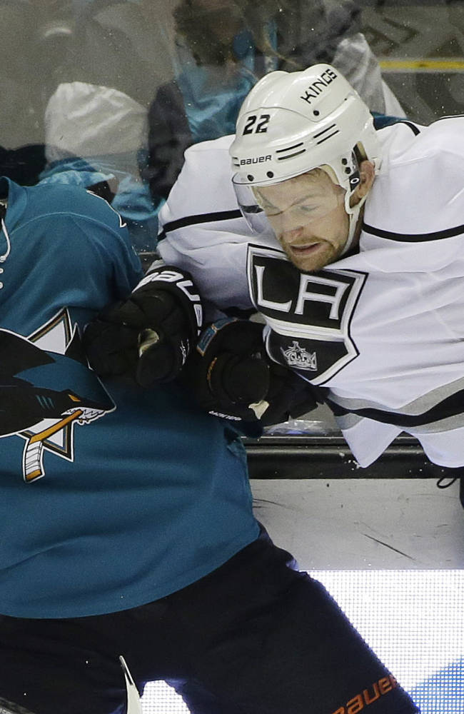 Los Angeles Kings' Trevor Lewis (22) collides with San Jose Sharks' Brad Stuart (7) during the third period of an NHL hockey game on Monday, Jan. 27, 2014, in San Jose, Calif. Los Angeles won 1-0
