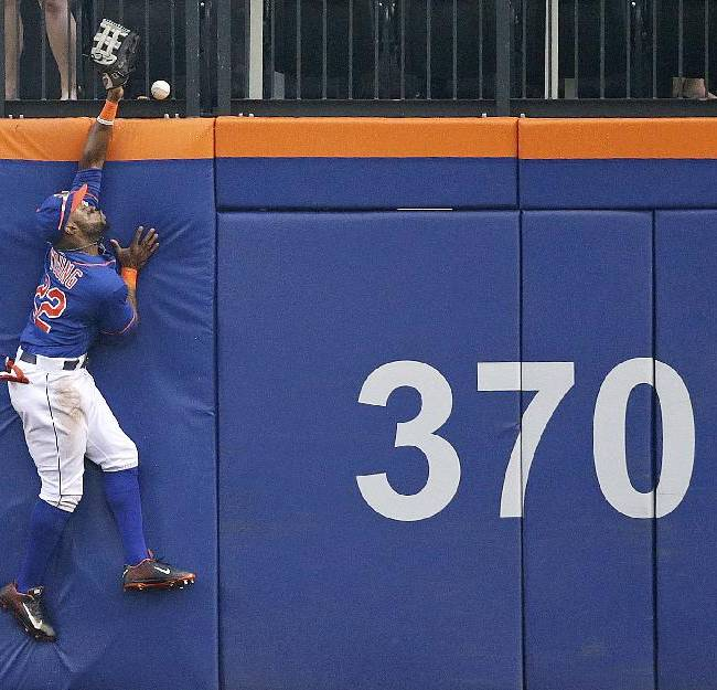New York Mets left fielder Eric Young Jr. leaps in vain at the wall trying to catch a solo home run hit by Washington Nationals' Adam LaRoche in the second inning of a baseball game, Thursday, Sept. 12, 2013, in New York. The umpires reviewed the play using video replay and ruled it a home run