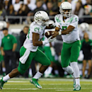 Oregon quarterback Marcus Mariota (8) hands off to running back Thomas Tyner (24) during the second quarter of an NCAA college football game against South Dakota in Eugene, Ore., Saturday, Aug. 30, 2014 The Associated Press