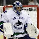 Vancouver Canucks goalie Roberto Luongo keeps his eyes trained on a rebound after a shot from the Dallas Stars in the first period of an NHL hockey game, Thursday, Dec. 19, 2013, in Dallas. (AP Photo/Tony Gutierrez)