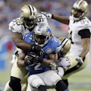 Detroit Lions running back Reggie Bush (21) is stopped by New Orleans Saints middle linebacker Curtis Lofton (50) and defensive back Marcus Ball (36) during the first half of an NFL football game in Detroit, Sunday, Oct. 19, 2014 The Associated Press