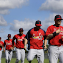St. Louis Cardinals catcher Yadier Molina, right, leads a group including, continuing from right to left, Matt Adams, Oscar Taveras, Rafael Ortega and Jhonny Peralta as they warm up at the start of spring training baseball practice Tuesday, Feb. 18, 2014,