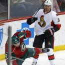 Ottawa Senators' Marc Methot, right, sends Minnesota Wild's Sean Bergenheim of Finland to the ice with a check in the first period of an NHL hockey game, Tuesday, March 3, 2015, in St. Paul, Minn. (AP Photo/Jim Mone)