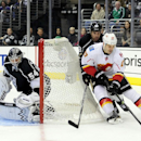 Calgary Flames left wing Lance Bouma, front right, moves the puck past Los Angeles Kings defenseman Willie Mitchell, back right, as goalie Ben Scrivens (54) is near during the first period of an NHL hockey game Saturday, Nov. 30, 2013, in Los Angeles The