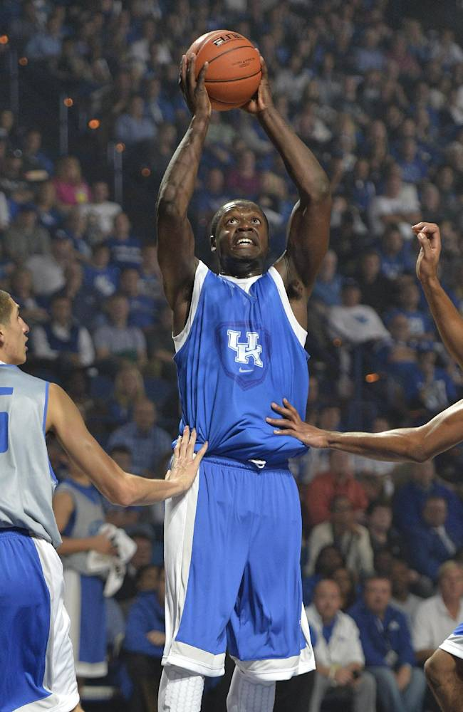 Julius Randle, center, gets a shot off between the defensive pressure of Derek Willis, left, and Marcus Lee during action of Kentucky's Big Blue Madness scrimmage Friday, Oct. 18, 2013 in Lexington, Ky