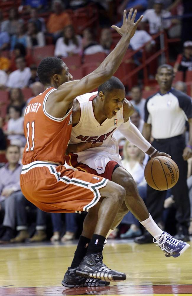 Miami Heat guard Mario Chalmers, right, drives around Milwaukee Bucks guard Brandon Knight (11) during the first half of an NBA basketball game on Wednesday, April 2, 2014, in Miami