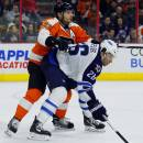 Philadelphia Flyers' Mark Streit (32), left, uses his stick to hold down Winnipeg Jets' Blake Wheeler as the two watch the action from near the Flyer's net in the third period of an NHL hockey game, Thursday, Jan. 29, 2015, in Philadelphia. The Flyers won 5-2. (AP Photo/Tom Mihalek)