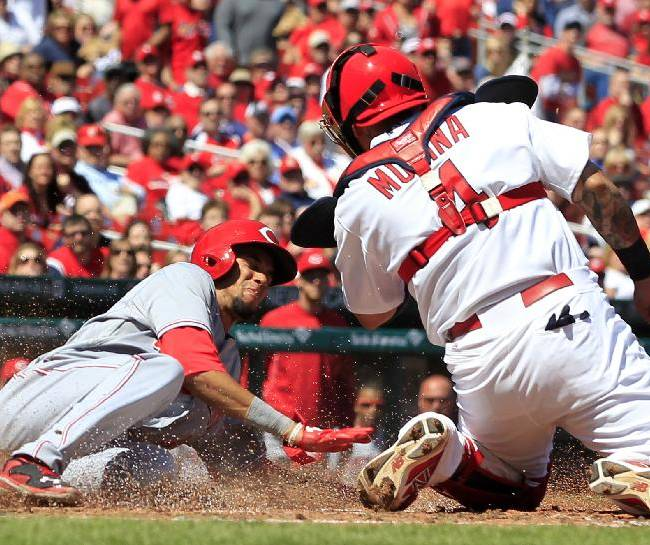 Cincinnati Reds' Billy Hamilton, left, scores ahead of the tag from St. Louis Cardinals catcher Yadier Molina on a sacrifice fly by Jay Bruce during the fifth inning of a baseball game Wednesday, April 9, 2014, in St. Louis