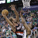 Portland Trail Blazers' Robin Lopez (42) shoots as Utah Jazz's Alec Burks, right, defends in the first quarter during an NBA basketball game on Friday, April 11, 2014, in Salt Lake City The Associated Press