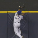 Milwaukee Brewers outfielder Carlos Gomez can't reach a home run by St. Louis Cardinals' Jhonny Peralta during the second inning of the MLB National League baseball game Monday, April 14, 2014, in Milwaukee The Associated Press
