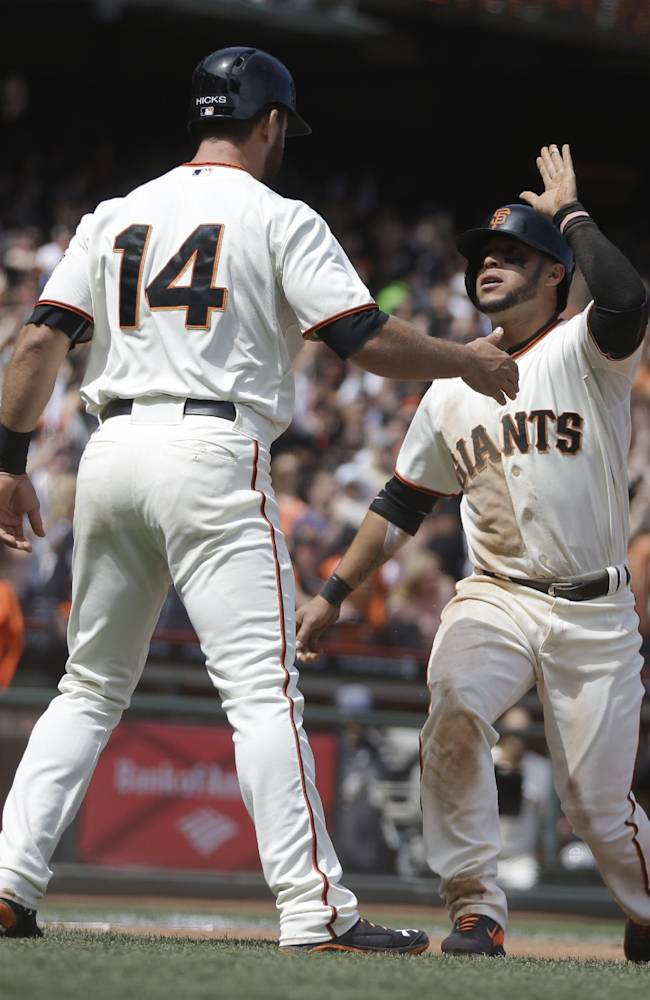 San Francisco Giants' Brandon Hicks (14) and Gregor Blanco celebrate after scoring against the Cleveland Indians in the fifth inning of a baseball game on Saturday, April 26, 2014, in San Francisco. They scored on a single hit by Hunter Pence