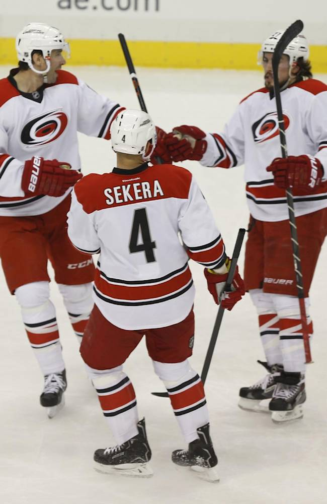 Carolina Hurricanes' Justin Faulk (27) celebrates scoring a goal with teammates Andrej Sekera (4), and Radek Dvorak (18), of the Czech Republic, during the first period of an NHL hockey game against the Pittsburgh PenguinsonTuesday, April 1, 2014, in Pittsburgh