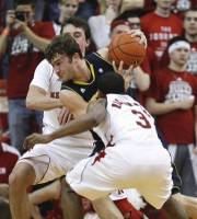 Michigan's Zack Novak, center, drives through Nebraska's Mike Fox, rear, and Brandon Richardson (3) in the first half of their NCAA college basketball game in Lincoln, Neb., Wednesday, Feb. 8, 2012. (AP Photo/Nati Harnik)