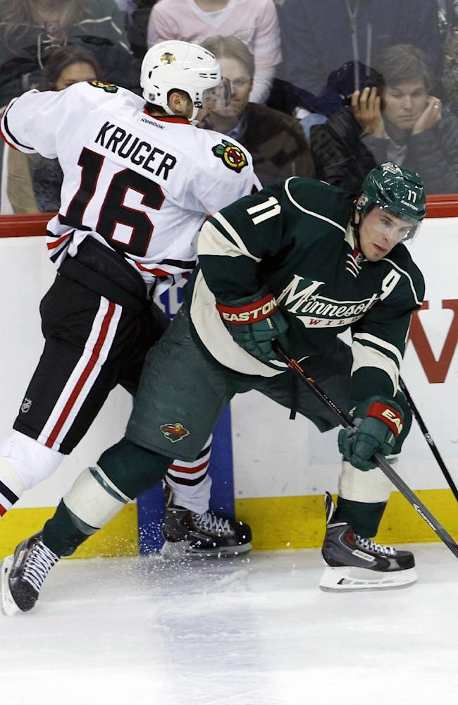 Minnesota Wild left wing Zach Parise (11) controls the puck in front of Chicago Blackhawks center Marcus Kruger (16) during the first period of Game 3 of an NHL hockey second-round playoff series in St. Paul, Minn., Tuesday, May 6, 2014