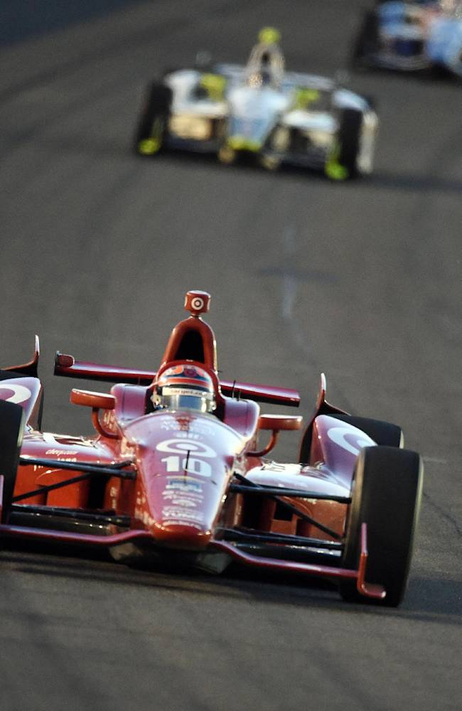 Tony Kanaan races into turn one during the opening laps of the IndyCar Series season final 500 mile auto race Saturday, Aug. 30, 2014, at Auto Club Speedway, in Fontana, Calif