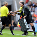 Referee Martin Atkinson, left, exchanges a can of vanishing spray with fourth official Neil Swarbrick, right, after his stopped working, during the English Premier League soccer match between Newcastle United and Manchester City at St James' Park, Newcast