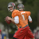Tampa Bay Buccaneers quarterbacks Josh McCown, front, and Mike Glennon drop back to throw a pass during NFL football training camp in Tampa, Fla., Friday, July 25, 2014 The Associated Press