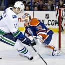 Vancouver Canucks' Radim Vrbata (17) is stopped by Edmonton Oilers goalie Ben Scrivens (30) during first-period NHL hockey game action in Edmonton, Alberta, Friday, Oct. 17, 2014 The Associated Press