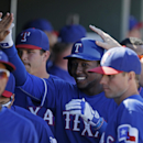 Texas Rangers' Jurickson Profar is congratulated in the dugout after hitting a solo home run during the third inning of a spring exhibition baseball game, Monday, March 10, 2014, in Suprise, Ariz. (AP Photo/Darron Cummings)