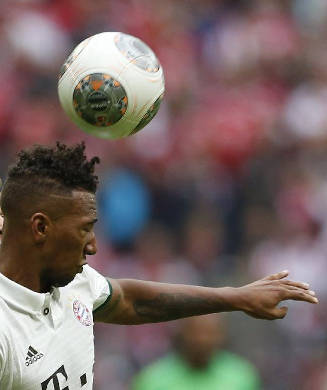 Hannover's Artur Sobiech of Poland,  left, , and Bayern's Jerome Boateng challenge for the ball during the German first division Bundesliga soccer match between FC Bayern Munich and Hannover 96, in Munich, southern Germany, Saturday, Sept. 14, 2013