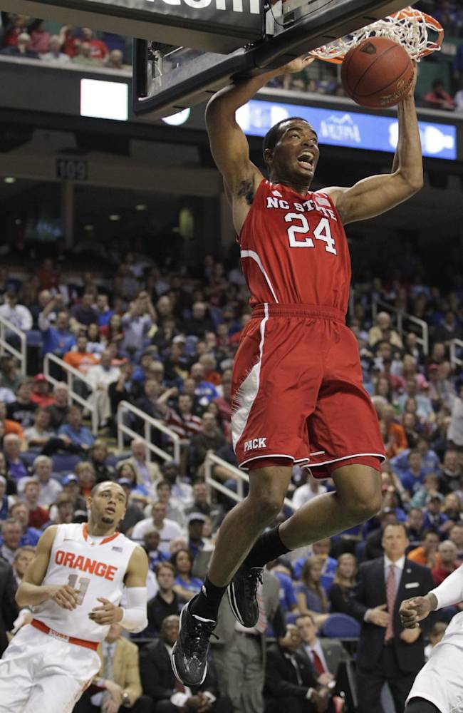 North Carolina State's T.J. Warren (24) dunks as Syracuse's Tyler Ennis (11) watches during the second half of a quarterfinal NCAA college basketball game at the Atlantic Coast Conference tournament in Greensboro, N.C., Friday, March 14, 2014