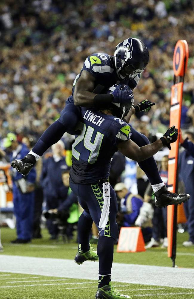 Seattle Seahawks' Derrick Coleman jumps on Seahawks' Marshawn Lynch (24) after Lynch scored his second touchdown of the second half of an NFL football game against the  San Francisco 49ers, Sunday, Sept. 15, 2013, in Seattle