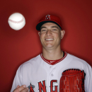 In this photo taken Saturday, Feb. 28, 2015, Los Angeles Angels' Garrett Richards tosses a ball during the team's photo day in Tempe, Ariz. Richards is expected to begin pitcher fielding drills in about a week as he makes progress from August knee surgery, and the club remains hopeful he could be pitching in games two to three weeks into the regular season for the reigning AL West champions. (AP Photo/Morry Gash)