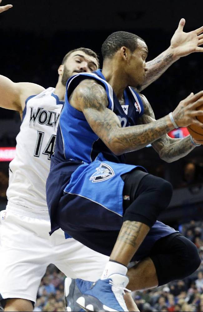 Dallas Mavericks' Monta Ellis, right, begins a layup as Minnesota Timberwolves' Nikola Pekovic, of Montenegro, defends in the second half of an NBA basketball game, Monday, Dec. 30, 2013, in Minneapolis. The Mavericks won 100-98