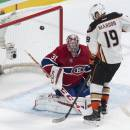 The puck flies away as Montreal Canadiens goalie Carey Price makes a save off Anaheim Ducks' Patrick Maroon during the second period of an NHL hockey game, Thursday, Dec. 18, 2014, in Montreal. (AP Photo/The Canadian Press, Paul Chiasson)