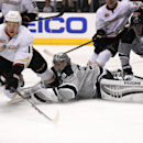 Anaheim Ducks center Nick Bonino, left, falls over Los Angeles Kings goalie Jonathan Quick just before scoring as center Anze Kopitar, right, of Slovenia, watches during the first period of an NHL hockey game, Saturday, April 12, 2014, in Los Angeles The